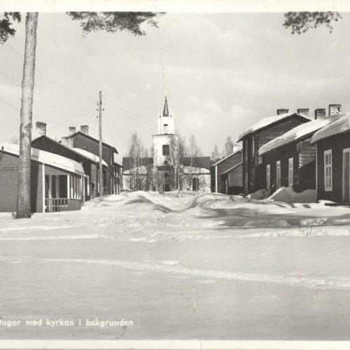 Kyrkstugor med kyrkan i bakgrunden