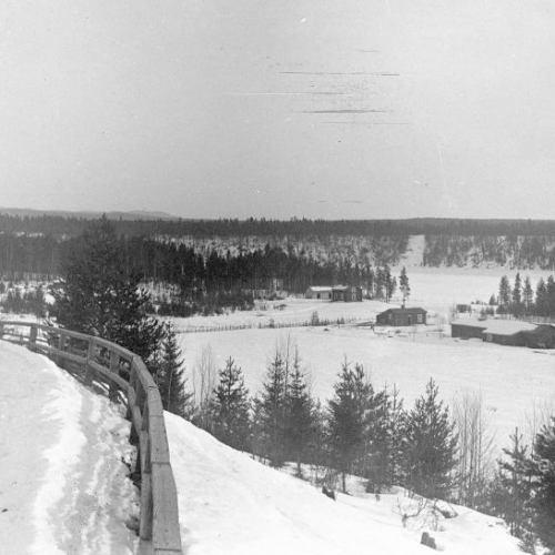 Utsikt från Lundgrensbacken i Vidsel mot kronojägarbostaden vid älven. Bilden troligen från ca 1920. Foto: A.R. Enberg